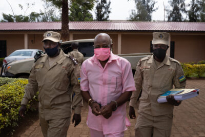 """(FILES) In this file photograph taken on October 2, 2020, """"Hotel Rwanda"""" hero Paul Rusesabagina (C) wears a pink prison inmate's uniform as he arrives at Nyarugenge Court of Justice in Kigali, flanked by guards of The Rwanda Correctional Service (RCS)"""